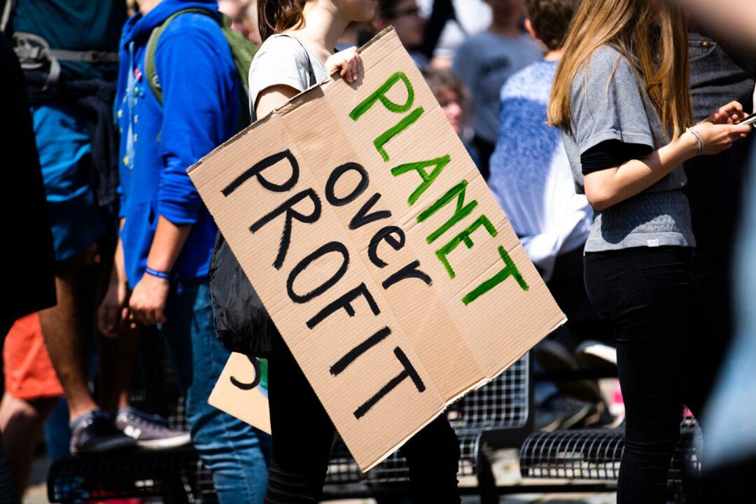 Activist holding a Planet Over Profit banner